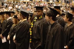 waiting graduates in cap and gowns - African American student facing camera