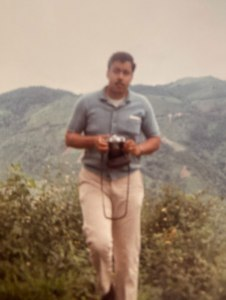 Charles with a camera and mountains in the background