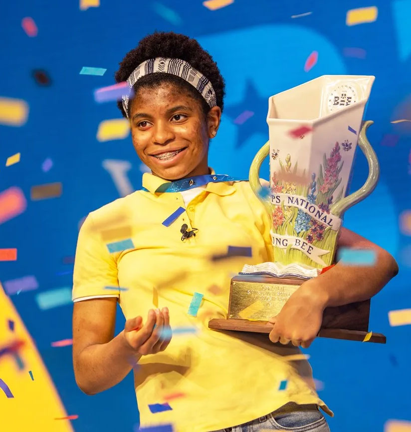 Zaila Avant-garde holding national spelling bee trophy with confetti coming down